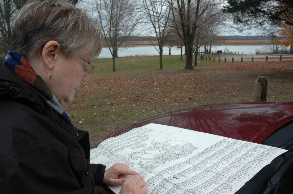 Susan Tichy at Magruder's Ferry, with map of early plantations in Prince George's County. Photo: Margaret Yocom, 2013.